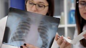 Dwa żeńskiego kobieta lekarza medycynego patrzeje promieniowania rentgenowskie w szpitalu zbiory