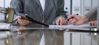 Dwa żeńskiego księgowego liczy na kalkulatora dochodzie dla podatek formy ukończenia, ręki zbliżenie Urząd skarbowy Obrazy Royalty Free