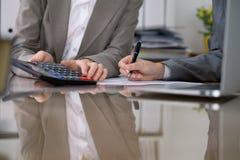 Dwa żeńskiego księgowego sprawdza sprawozdanie finansowe lub liczenie kalkulatora dochodem dla podatek formy, ręki zakończenie Zdjęcia Stock