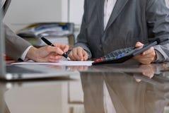 Dwa żeńskiego księgowego sprawdza sprawozdanie finansowe lub liczenie kalkulatora dochodem dla podatek formy, ręki zakończenie Zdjęcia Royalty Free