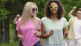 Dwa żeńskiego przyjaciela tanczy i opowiada przy przyjęciem w parku, faceci cieszy się lato zdjęcie wideo