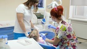 Dwa żeńskiego stomatologists przy pracą taktują chorych zęby dziecko w szpitalu z specjalnym narzędziem w ręce zdjęcie wideo