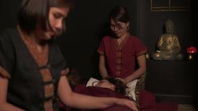 Dwa żeńskiego tajlandzkiego terapeuta robi masażowi dla kobiety w zdroju salonie Dwa wręczali tajlandzkiego masaż nogi i głowa 4k zdjęcie wideo