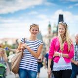 Dwa żeńskiego turysty chodzi wzdłuż Charles mosta zdjęcia stock