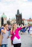 Dwa żeńskiego turysty chodzi wzdłuż Charles mosta obrazy stock
