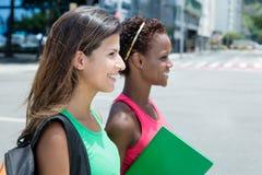 Dwa żeńskiego ucznia chodzi w mieście w lecie Zdjęcia Stock
