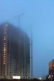 Dwa żurawia na budowie, niedokończeni domy, mgła zakrywają górne piętra, evening zmierzch oświetlenie Zdjęcie Stock