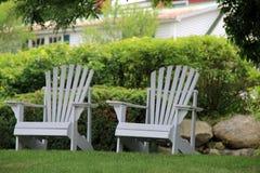 Dwa Adirondack krzesła na trawniku przed domem Zdjęcia Royalty Free