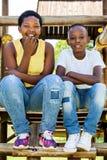 Dwa afrykańskiego dzieciaka siedzi na drewnianej strukturze w parku fotografia royalty free