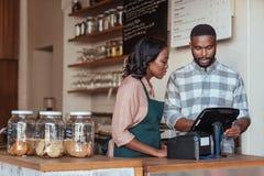 Dwa Afrykańskiego przedsiębiorcy pracuje za ich kawiarnia kontuarem obraz royalty free