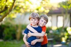 Dwa aktywnego mała szkoła żartuje chłopiec, bliźniaków i rodzeństwa ściska na letnim dniu, obrazy royalty free