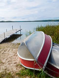 Dwa aluminiowej łodzi ciągnęli up na brzeg z dokiem w tle Fotografia Stock