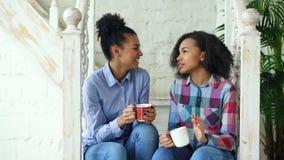 Dwa amerykanin afrykańskiego pochodzenia dziewczyn kędzierzawego sistres siedzi na schodkach zabawę śmia się wpólnie w domu i gaw Zdjęcia Royalty Free
