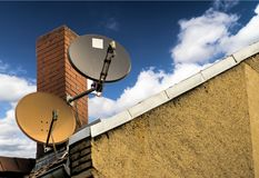 Dwa anteny satelitarnej przed czerwonej cegły kominem na połogim dachu dom zdjęcia royalty free