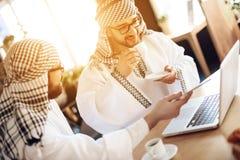 Dwa arabskiego biznesmena pije kawę przy stołem przy pokojem hotelowym zdjęcia stock
