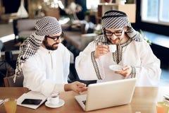Dwa arabskiego biznesmena pije kawę przy stołem przy pokojem hotelowym obrazy royalty free