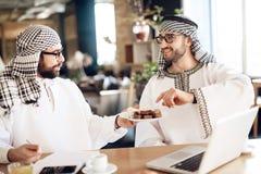 Dwa arabskiego biznesmena przy stołem przy pokojem hotelowym z jeden trzyma tureckim zachwytem fotografia stock