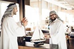Dwa arabskiego biznesmena z wzorcowym jachtem przy stołem przy pokojem hotelowym obrazy stock