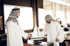 Dwa arabskiego biznesmena z wzorcowym jachtem przy stołem przy pokojem hotelowym obraz royalty free