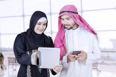 Dwa Arabskiego pracownika używa pastylkę fotografia royalty free