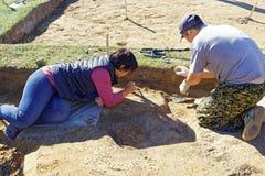 Dwa archeologa ostrożnie wykopują antycznego grób Obraz Royalty Free