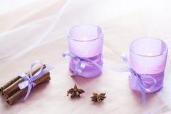 Dwa aromatycznej świeczki w szklanych candlesticks z papierem, cynamonem i anyżem na stołu zakończeniu up lawendy, Obrazy Stock