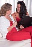 Dwa atrakcyjna kobieta siiting na leżance dyskutuje notatkę i bierze zdjęcie royalty free