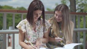 Dwa atrakcyjnego żeńskiego ucznia siedzi outdoors wpólnie dyskutujący pracę domową, pisze puszku w notatnikach Lato zbiory wideo