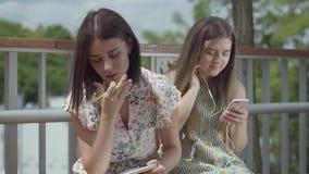Dwa atrakcyjnego żeńskiego ucznia siedzi outdoors wpólnie Jeden dziewczyna słucha muzyka z jej hełmofonami, po drugie jeden zbiory