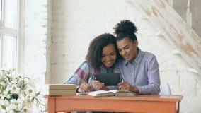 Dwa atrakcyjnej kędzierzawej z włosami mieszanej biegowej młodej dziewczyny siedzi przy stołem zabawę podczas gdy uczący się lekc zbiory