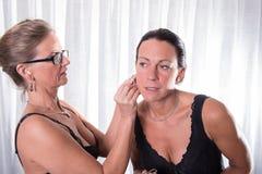 Dwa atrakcyjnej kobiety - jeden stawia inny dalej jej kolczyk zdjęcia royalty free