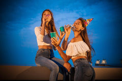 Dwa atrakcyjnej młodej kobiety witają podmuchowego urodziny trąbka, świętują i podnoszą ich ręki zdjęcia stock