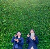 Dwa azjata bizneswomanu mienia pastylka i punktu palec do ai Zdjęcia Stock