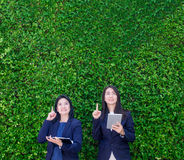 Dwa azjata bizneswomanu mienia pastylka i punktu palec do ai Fotografia Royalty Free