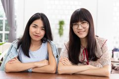 Dwa azjata dziewczyny obsiadania wpólnie nastoletni spojrzenie i uśmiech zdjęcie royalty free