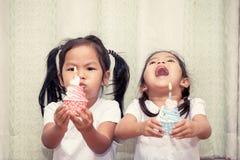 Dwa azjata mała dziewczynka ma zabawę podmuchowa urodzinowa babeczka Obrazy Stock