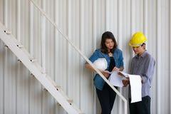 Dwa Azjatyckiego inżyniera mężczyzna i kobieta dyskutuje w budowie, zdjęcie royalty free