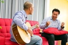 Dwa azjatykciego faceta bawić się gitarę, muzyczny instrument dla szczęśliwy obraz royalty free