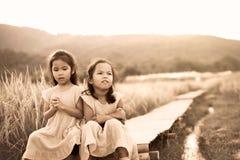 Dwa azjatykciej małe dziecko dziewczyny która czują zanudzają i smutny Obraz Royalty Free