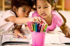 Dwa azjatykciej małej dziewczynki ma zabawę wybierać kredkę Obrazy Royalty Free