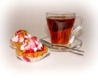 Dwa babeczka i filiżanka herbata na białym tle Zdjęcia Stock