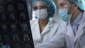 Dwa badacza studiuje ludzkiego mózg MRI, analizuje swój warunek i dyskutuje, zbiory wideo