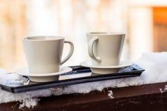 Dwa beżowego kubka z gorącymi napojami na krawędzi balkonu z śniegiem na stronach i śnieżnej naturze w tle, fotografia royalty free