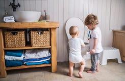 Dwa berbecia dziecka z toothbrush pozycją toaletą w łazience w domu Obraz Stock