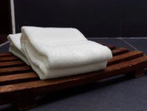Dwa białego fałdowego ręcznika stawiali na drewnianej lath tacy, koszu nad tłem ciemnym lub czarnym lub obraz stock