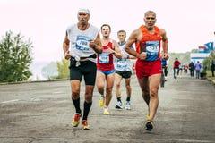 Dwa biegaczów starszy bieg naprzeciw wielkiej grupy biegacze Fotografia Royalty Free