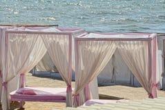 Dwa biel różowy otwarty gazebo z zasłony poduszką i pościel na piasku na plaży przeciw morzu zdjęcia stock