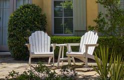 Dwa bielu adirondack krzesła siedzi na patiu przed okno z zieleni żaluzjami i żywopłotem z roślinami wokoło one zdjęcia royalty free