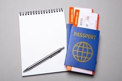 Dwa bileta dla samolotu z paszportami i notatnika z piórem na szarym tle Fotografia Stock