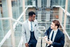 Dwa biznesmenów multiracial dyskusja w nowożytnej sala obrazy royalty free